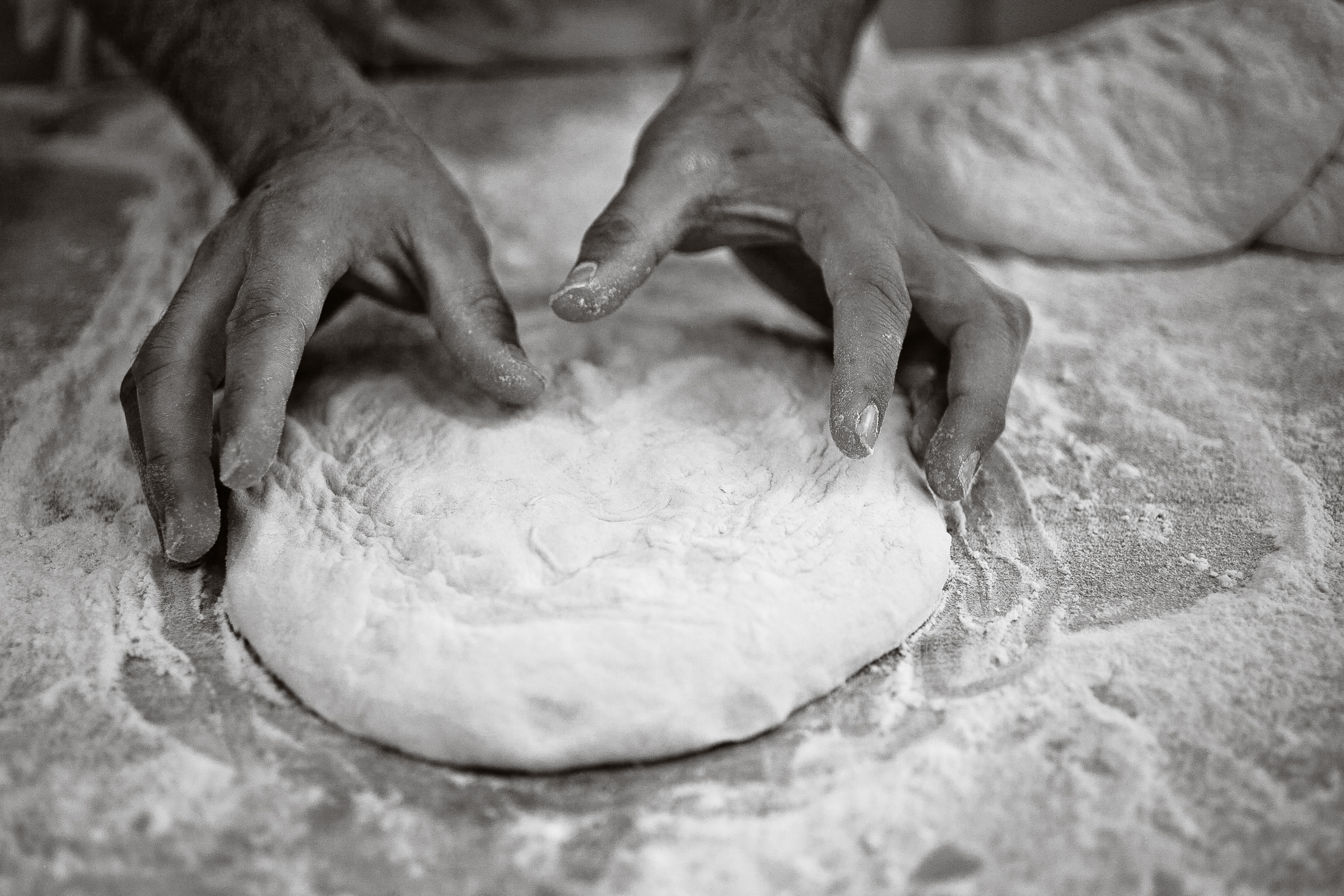 photo of hands kneading pizza dough
